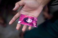 A National League of Democracy supporter holds a laminated card of Aung San Suu Kyi outside her party headquarters the day after her release from house arrest in Rangoon. From 1990 until her release on 13 November 2010, Aung San Suu Kyi had spent almost 15 of the 21 years under house arrest.