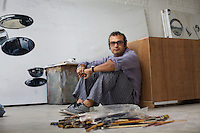 Subodh Gupta, contemporary artist with works-in-progress in his recently completed studio in Gurgaon, a satellite town of Delhi...Gupta's most celebrated sculptures are constructed from common domestic items including the steel pots and pans that are a feature every Indian home. Of the kitchen-ware that forms the basis of his work, Gupta says,..&quot;The poor, the middle class and the rich use it at home. In this country, how many people have the utensils but they starve because there is no food?&quot;..Gupta was brought up, one of six children, to a railway-worker father in a north Indian village. ..Gupta's work fetches such huge sums of money. Two versions of his Mind Shut Down, modeled on the human skull and constructed entirely of steel kitchen utensils recently sold for EUR1 million each...Photo: Tom Pietrasik.Gurgaon, Haryana. India. .June 26th 2009