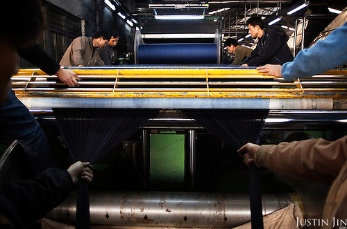 "Workers dye cotton threads for weaving into denim in Zhongshan city, China. .This picture is part of a photo and text story on blue jeans production in China by Justin Jin. .China, the ""factory of the world"", is now also the major producer for blue jeans. To meet production demand, thousands of workers sweat through the night scrubbing, spraying and tearing trousers to create their rugged look. .At dawn, workers bundle the garment off to another factory for packaging and shipping around the world..The workers are among the 200 million migrant labourers criss-crossing China.looking for a better life, at the same time building their country into a.mighty industrial power."