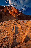 792980045 low angled sunset light highlights the sandstone formations and red rock mountains giving a three dimensional effect to the scene in valley of fire state park nevada