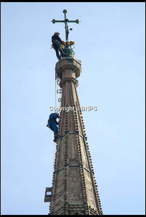 BNPS.co.uk (01202 558833)<br /> Pic: TomWren/BNPS<br /> <br /> Ecclesiastical carpenter Richard Pike heads up the spire.<br /> <br /> How many men does it take to change a lightbulb... at the top of Britain's tallest spire.<br /> <br /> When your office is Salisbury Cathedral the simple task of changing a light bulb involves four men, a 404ft climb and takes three hours.<br /> <br /> Ecclesiastical carpenter Richard Pike needed a head for heights when he joined Gary Price, who is in charge of conservation, to make the daring ascent with two rope specialists to ensure their safety. <br /> <br /> Despite working at the cathedral for 27 years, it was the first time Richard has ever made the hair-raising climb.