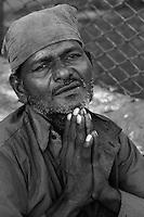 The streets of Mumbai India, a man beggar sitting in the streets of Mumbai near the Bollywood area