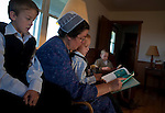 Mary Ethel Rhodes reads a story to Glenn and his younger brother Jesse before leaving for Sunday services. Sunday mornings are somber as families prepare for their church service. After the children are dressed in their Sunday best, they read or do quiet activities until they leave for church.