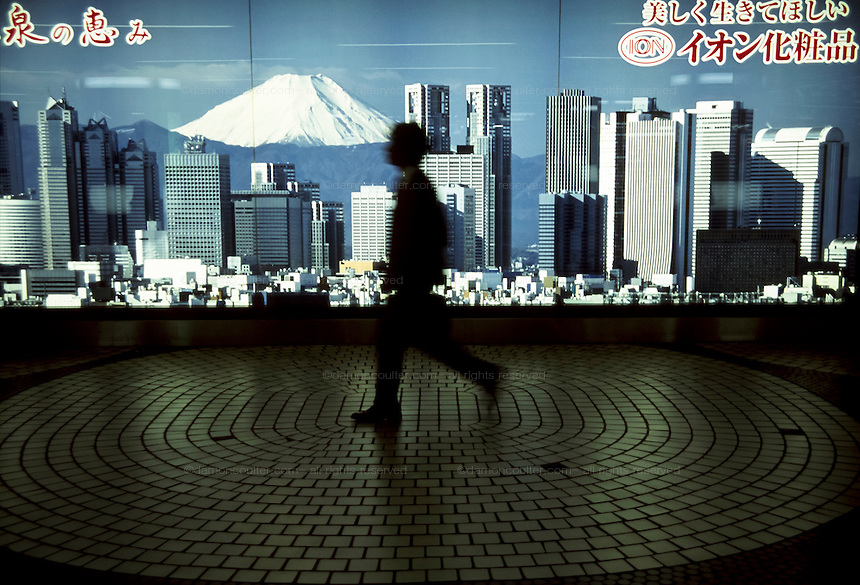 A man walks passed an advertising poster depticting the Tokyo skyline and Mount Fuji in Shinjuku Station, Tokyo Japan March 19th 2005
