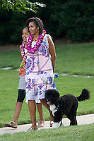 25 Jun 2009, Washington, DC, USA --- First lady Michelle Obama and daughter Malia walk from the Oval Office with their dog Bo as they attend a luau, or Hawaiian feast, on the South Lawn of the White House for members of Congress and their families in Washington. --- Image by © Brooks Kraft/Corbis