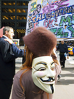 USA. New York City. Occupy Wall Street (OWS) is a people-powered movement that began on September 17, 2011 in Liberty Square in the Wall Street financial district of Manhattan. The protesters have created a small campsite at the Zuccotti Park site. OWS and has spread to over 100 cities in the United States and actions in over 1,500 cities globally. OWS is mainly protesting social and economic inequality, corporate greed, corruption and influence over government&mdash;particularly from the financial services sector&mdash;and lobbyists.  It is fighting back against the corrosive power of major banks and multinational corporations over the democratic process, and the role of Wall Street in creating an economic collapse that has caused the greatest recession in generations. The protesters' slogan, &quot;We are the 99%&quot;, refers to the difference in wealth and income growth in the U.S. between the wealthiest 1% and the rest of the population. OWS aims to expose how the richest 1% of people are writing the rules of an unfair global economy that is foreclosing on our future. OWS has being organized using a non-binding consensus based collective decision making tool known as a &quot;people's assembly&quot;. A woman with the Guy Fawkes mask on the back of her head. The Guy Fawkes mask is the face of a dead man, the visage of Vendetta, in comic books and a popular Hollywood film; but mostly the avatar of Anonymous, the group of hacktivists who are legion online; and the image worn by Occupy Wall Street activists. 20.10.2011 &copy; 2011 Didier Ruef