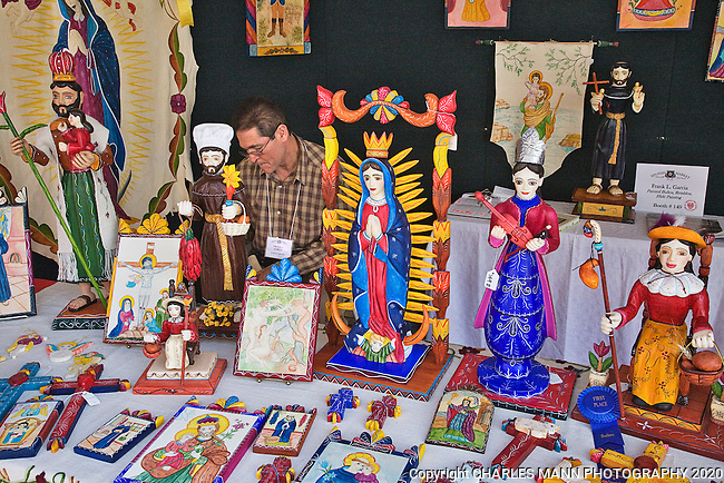 The Santa Fe Spanish Market, held in late July, fills the Santa Fe Plaza with artists, patrons and visitors all celebrating the richness of the Spanish Colonial art tradition side by side with the Contemporary Spanish Art Market. Frank L. Garcia presents visitors with a choice of  colofrul bultos, retablos and hide paintings.