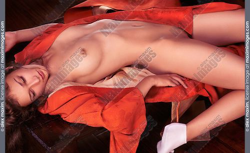Erotic photo of a beautiful naked young japanese woman in red kimono lying on a tea table