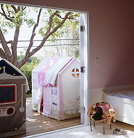 The deck outside the children's bedroom has 'his and hers' play tents