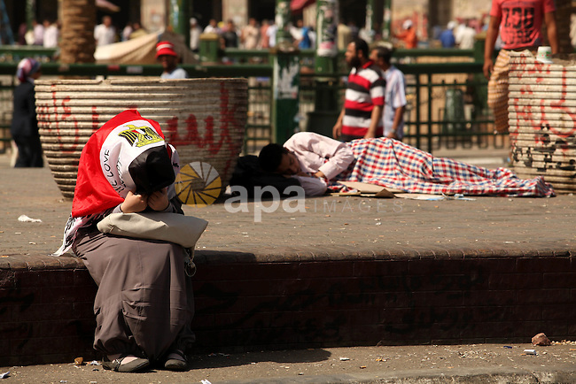 Egyptian men sleep on the ground in Cairo's landmark Tahrir Square on June 3, 2012 after a night of protests. Hundreds of demonstrators are occupying Tahrir Square after a court sentenced ousted president Hosni Mubarak and his interior minister Habib al-Adly to life in prison but acquitted six security chiefs in the deaths of protesters last year. Photo by Majdi Fathi
