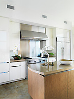 This spacious kitchen is modern and functional with cast concrete work surfaces and a large stainless steel cooker