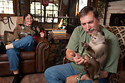 Dave Viguers and Eldon, a Cinnamon Capuchin monkey, spend time together inside the house. Dave's wife, Sandy Viguers, watches them play.  Dave and Sandy Viguers live with monkeys at their home outside of Lampasas, Texas.  February 22, 2009.