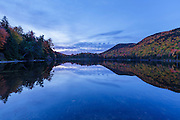 Reflection of autumn foliage in Upper Hall Pond in Sandwich, New Hampshire USA during morning blue hour.