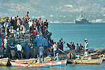 Residents of Port-au-Prince, Haiti, unload food and other supplies from a ferry from Jeremie. The ferry is bringing food into the capital and allowing thousands to flee the city, which was devastated by a January 12 earthquake. A U.S. Navy warship can be seen in the background. As many as 200,000 people may have already left Port-au-Prince, seeking better conditions elsewhere in the Caribbean island nation.