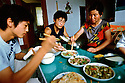 "7/15/2005--Nanjie Village, Henan Province, China..Wang Zhi Lei, 22 (center: see text for details), his mother Zhai Cui Ling, 44 (right) and brother (left) eating food provided for free by Nanjie village, a model communist village in the central province of Henan. Nanjie collectivised its agricultural production and industry in the mid 1980s - when the rest of the country was doing the opposite, introducing market reforms put forward by former leader Deng Xiaoping. Although the teachings of the ""Great Helmsman"" serve as the moral compass for the 3,100 people of Nanjie, the real secret to its collective well-being is, well, capitalist: two dozen village enterprises manufacturing all sorts of things ? noodles, beer, pharmaceuticals. One even promotes ""red tourism.""..It continues to be run on Maoist egalitarian lines and has become something of a tourist attraction because of its staunch adherence to the values of the past. .Photograph By Stuart Isett.All photographs ©2005 Stuart Isett.All rights reserved."