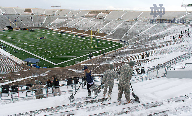 Nov. 14, 2014; Members of the Notre Dame Army ROTC battalion shovel snow out of Notre Dame Stadium the day before the game against Northwestern. (Photo by Matt Cashore)
