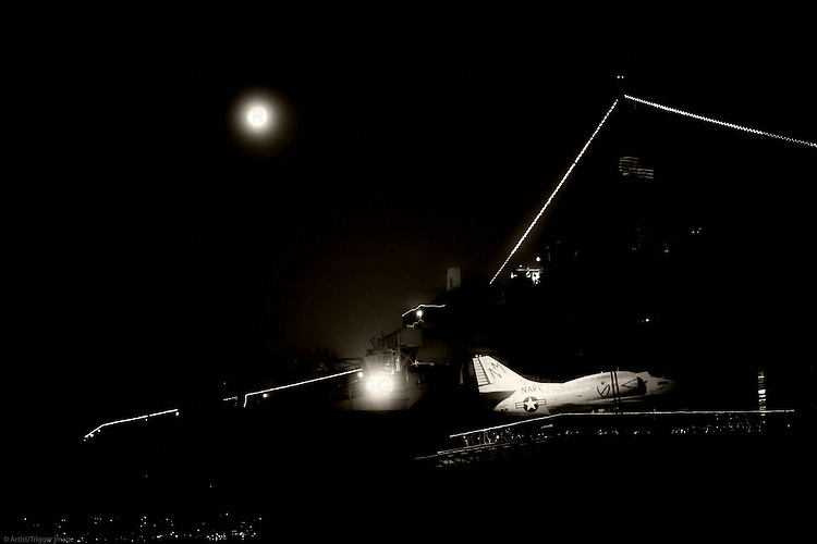 An old fighter plane stands on the nocturnal lit deck of the aircraft carrier and museum ship MSS Midway in Navy Pier.