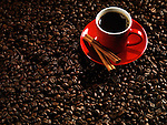 Red cup of coffee on coffe beans background