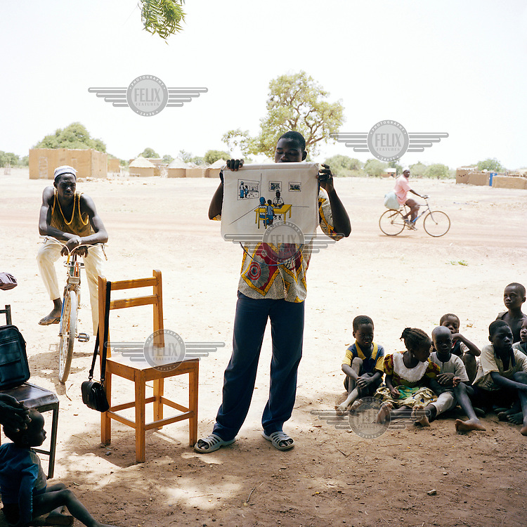 A man teaches children about malaria in a remote village in Namentenga.