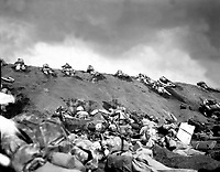 Marines of the 5th Division inch their way up a slope on Red Beach No. 1 toward Surbachi Yama as the smoke of the battle drifts about them.  Iwo Jima, February 19, 1945.  Dreyfuss.  (Marine Corps)<br /> NARA FILE #:  127-N-110249<br /> WAR &amp; CONFLICT BOOK #:  1217