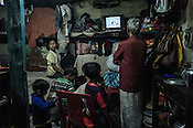 A family sits in their one-room house to watch the India-Pakistan cricket match at Park Circus in Kolkata, West Bengal, India.