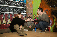 15 December 2006 - New York City, NY - Curators (LtoR) Sara and Marc Schiller and Malcolm Stevenson sit and chat among artwork exposed in a three-day street art exhibition held inside a 19th-century brick building at 11 Spring Street in the NoLIta neighborhood of New York City, USA, 15 December 2006. The building's new owners, Caroline Cummings and Bill Elias, called on the Wooster Collective to curate the show as a last hurrah for a site that long served as a canvas for street art.<br />