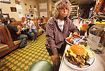 Where's the bun? ..The 32-oz Coffee Burger is one-of-a-kind burger prepared-to-order at Sioux Sundries in Harrison, Nebraska...Consisting of two one-pound patties of ground beef, six slices of golden American cheese, lettuce, tomatoes and pickles all served on a regular hamburger bun with lots of napkins. ..When you order, everyone stares at you in disbelief. It takes about a half-hour to prepare and nearly as long to eat it all. ..Here, Carolyn Fox wonders how we're going to eat the whole thing.....The only way to find such American delacacies is to go out in and stumble upon it. You won't find this sitting at your desk!