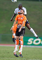 Zat Knight of the Bolton Wanderers jumps over Kieren Keane of the Charlotte Eagles.  The Charlotte Eagles currently in 3rd place in the USL second division play a friendly against the Bolton Wanderers from the English Premier League.