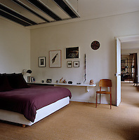 In the master bedroom a canopy in minimalist contemporary style is suspended over the bed and a long shelf on an adjacent wall displays a collection of small sculptures and mementos