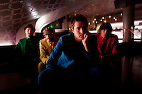 """Los Angeles, California, November 27, 2010 - A portrait of the band Ok Go, from left, drummer, Dan Konopka (green), bass guitarist/singer, Tim Nordwind (yellow), lead singer/guitarist, Damian Kulash (blue), and guitarist/singer, Andy Ross (red), in the VIP lounge at the Nokia Club. OK Go was wrapping up a 16-month world tour by playing a song for Yo Gabba Gabba! during the day and later a final show at the Nokia Club. The Grammy Award-winning band has earned considerable fame for their creative, often low-budget music videos that are released on YouTube. Many have gone viral, including the 2006 video for """"Here It Goes Again"""", where the band performs a complex routine on treadmills. It has received over 50 million views to date. Kulash says the band left their major label and began their own to assert more creative control over their music and their videos. Adding, """"We're among the first musicians to view our YouTube videos as standalone artistic output, not advertisement for our recordings, and it shows in the numbers: over the past decade, we've sold a little over 600,000 records globally, and our videos have combined views in excess of 125 million.""""..."""