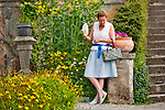 A woman carries a multi colored straw purse from Bellagio, Italy while visiting a garden at Villa Monastero in Varenna, Italy on Lake Como