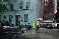 A woman walks along a sidewalk in the rain, holding a pink umbrella, through a window covered in water droplets.
