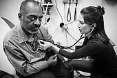 """Physician assistant Jen Vaupel listens to  Robert """"Bobby"""" Young's heart during a check up at Bread for the City in Washington, DC."""