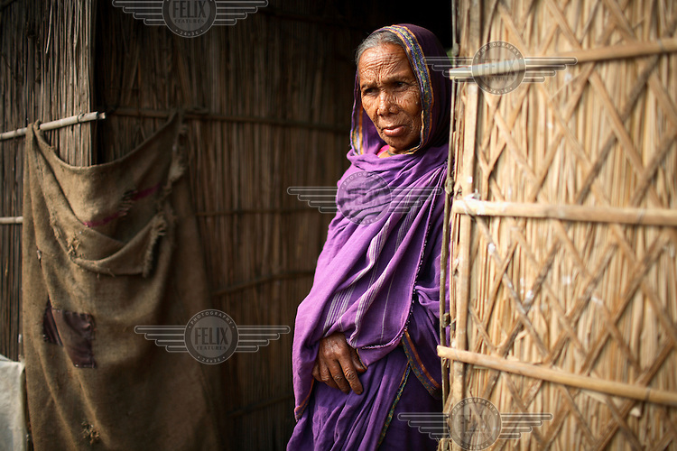 An elderly woman stands in the doorway to her home in the Dawabari river bed area. 'Chars' such as this - islands that are periodically submerged by the country's mighty rivers - are home to over five million people in Bangladesh. Life for the char dwellers is hazardous and uncertain. Flooding is common, as is loss of land and erosion, making it a struggle to grow enough food, and meaning families often need to relocate.
