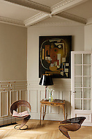 The decoration of the breakfast room includes a pair of 1950s circular cane chairs, an Art Nouveau side table and an abstract painting from the 1940s