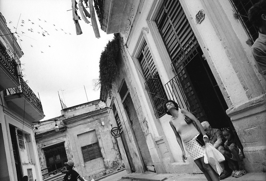 Pigeons fly overhead as a Havana resident looks up at the day's weather.