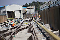 ALSTOM's employees (in purple hardhats) walk along the tracks, lined by the Third Line Power Supply rails (yellow rails), while some others work on the LED signalling lights and MJ81 - Intech Point Machines, at the Baiyappanahalli depot station in Bangalore, Karnataka, India on 10th March 2011. .Photo by Suzanne Lee/Abaca Press