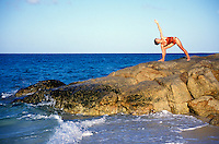Australia, Queensland, woman doing yoga on seaside rocks. MR available