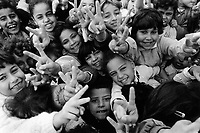 """State of Palestine. West Bank. Balata Camp. Palestinian refugees. Schoolgirls making V signs in UNRWA (United Nations Relief and Works Agency for Palestine Refugees in the Near East) schoolyard. The V sign is a hand gesture in which the index and middle fingers are raised and parted, while the other fingers are clenched. It has been used to represent the letter """"V"""" as in """"victory"""". Balata Camp is a Palestinian refugee camp established in the northern West Bank in 1950, adjacent to the city of Nablus. It is the largest refugee camp in the West Bank. Balata Camp is densely populated with 30,000 residents in an area of 0.25 square kilometers. In 1991, Balata Camp was living under Isreal's occupation and rules as part as the Occuppied Territories. In the 1980s and 1990s, Balata residents played a leading role in the uprisings known as the First Intifada and the Second Intifada. Balata Camp is since 1993 under palestinian authority, located in the A zone. The Palestinian National Authority (PA or PNA) was the interim self-government body established to govern Areas A and B of the West Bank as a consequence of the 1993 Oslo Accords. Following elections in 2006, its authority had extended only in areas A and B of the West Bank. Since January 2013, the Fatah-controlled Palestinian Authority uses the name State of Palestine on official documents. T © 1991 Didier Ruef"""