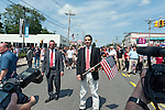 MAY 30, 2011 - LITTLE NECK, NY: New York Governor Andrew M. Cuomo marching in Little Neck-Douglaston Memorial Day Parade, with glimpse of cameras in foreground giving strong sense of depth, on Northern Boulevard on May 30, 2011.