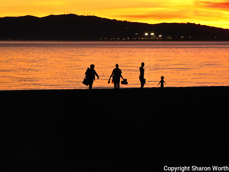 As the sunset paints the sky gold and orange, beach goers gather up belongings and prepare to end their day at Alameda Beach on the eastern shore of San Francisco Bay.