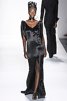 Model walks runway an EBONY COUTURE SILK SATIN SEXY V-RACK FRONT-SLIT GOWN W/ DRAPED SLEEVES by Zang Toi, for the Zang Toi Spring 2012 My Dream Of North Africa Collection, during Mercedes-Benz Fashion Week Spring 2012.