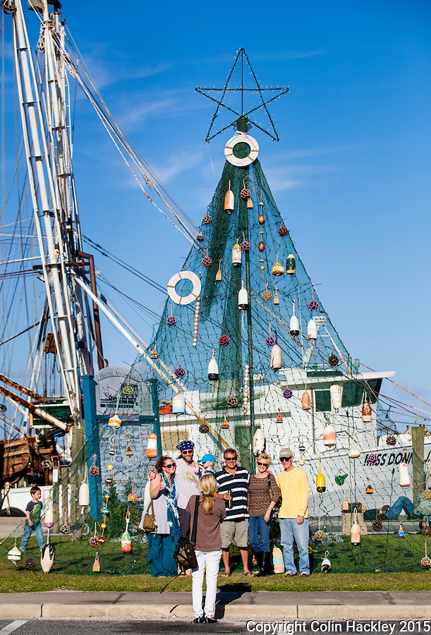 APALACHICOLA, FLA. 11/27/15-In Apalachicola the Christmas tree might be made from a fishing net with bouts and life rings for decorations. Here a group poses for a holiday photo with a Florida twist. <br /> <br /> COLIN HACKLEY PHOTO