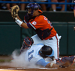 06/18/2006 University of North Carolina's Mike Cavasinni slides in safely  as Clemson catcher Adrian Casanova waits for the throw during game six of the College World Series in Omaha Nebraska Sunday evening..(photo by Chris Machian /Prairie Pixel Group)