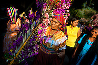 "A Salvadoran woman carries a palm branch with colorful flower blooms during the procession of the Flower & Palm Festival in Panchimalco, El Salvador, 8 May 2011. On the first Sunday of May, the small town of Panchimalco, lying close to San Salvador, celebrates its two patron saints with a spectacular festivity, known as ""Fiesta de las Flores y Palmas"". The origin of this event comes from pre-Columbian Maya culture and used to commemorate the start of the rainy season. Women strip the palm branches and skewer flower blooms on them to create large colorful decoration. In the afternoon procession, lead by a male dance group performing a religious dance-drama inspired by the Spanish Reconquest, large altars adorned with flowers are slowly carried by women, dressed in typical costumes, through the steep streets of the town."