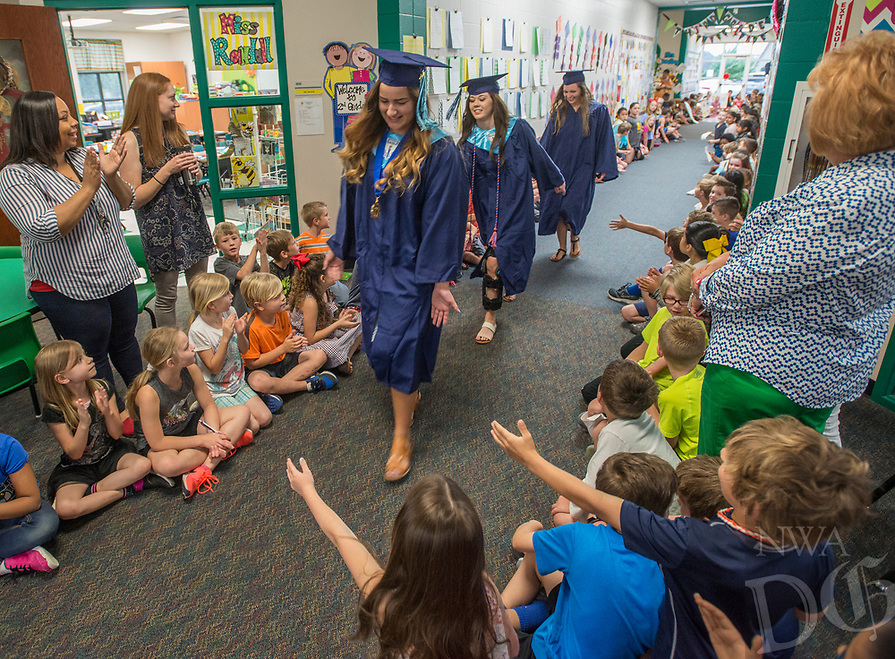 NWA Democrat-Gazette/ANTHONY REYES @NWATONYR<br /> Kennadi Kissinger a Springdale Har-Ber graduating senior, slaps hands Wednesday, May 17, 2017 with students at Young Elementary School in Springdale. Kissinger joined other Har-Ber seniors were once students at the elementary school and returned to walk and be congratulated by current students. The seniors were treated to a reunion with former teachers at a reception in the school's media center after the walk.