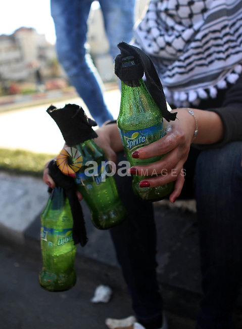 A female Palestinian protester holds molotov cocktails during clashes with Israeli security forces in Beit El on the outskirts of the West Bank city of Ramallah, November 29, 2015. Photo by Shadi Hatem