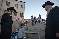 Ultra Orthodox kid perform the Kaparot ceremony on September 10, 2013 in Jerusalem, Israel. The Jewish ritual is supposed to transfer the sins of the past year to the chicken, and is performed before the Day of Atonement, or Yom Kippur, the most important day in the Jewish calendar, which this year will start on sunset on September 13.  Photo by Oren Nahshon