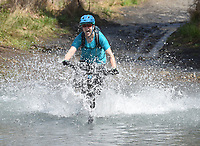NWA Democrat-Gazette/FLIP PUTTHOFF <br /> BIG BIKE SPASH<br /> Lindsay Custer of Bentonville hits Lee Creek at high speed Saturday April 8 2017 during the Lee Creek Cannonball Big Splash Contest, part of the 29th annual Ozark Mountain Bike Festival at Devil's Den State Park. About a dozen contestants were judged on the size of their splash and style going into the water. Jeremiah &quot;Scratch&quot; Stone of Rogers won the contest. Festival events included guided mountain bike rides for all skill levels, clinics on riding technique, a poker run, bike games for kids and a cookout. The festival ends today with a guided ride at 10:30 a.m.
