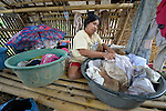Christina Balitor washes laundry at her home in Estancia, in the Philippines province of Iloilo. A survivor of childhood polio, she cannot walk on her own. She washes laundry to earn a meager living. Her wheelchair broke six years before and she has been unable to afford a new one. Her house was washed away by Typhoon Haiyan, known locally as Yolanda, in November 2013. Balitor now lives with her sister.
